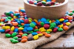 Красочные круглые конфеты шоколада на ткани мешка реднины на деревянной таблице Стоковое Изображение