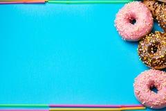 Красочные круглые donuts на голубой предпосылке Плоское положение, взгляд сверху Стоковое Изображение