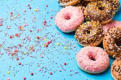 Красочные круглые donuts на голубой предпосылке Плоское положение, взгляд сверху Стоковая Фотография