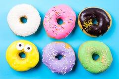 Красочные круглые donuts на голубой предпосылке Плоское положение, взгляд сверху Стоковое фото RF