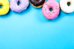 Красочные круглые donuts на голубой предпосылке Плоское положение, взгляд сверху Стоковые Изображения RF