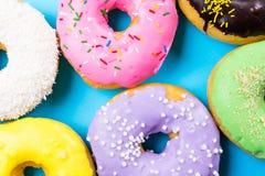 Красочные круглые donuts на голубой предпосылке Плоское положение, взгляд сверху Стоковые Изображения