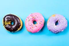 Красочные круглые donuts на голубой предпосылке Плоское положение, взгляд сверху Стоковые Фотографии RF