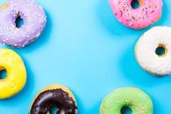 Красочные круглые donuts на голубой предпосылке Плоское положение, взгляд сверху Стоковое Фото