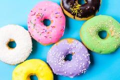 Красочные круглые donuts на голубой предпосылке Плоское положение, взгляд сверху Стоковые Фото