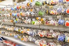 Красочные кружки вися на подносе покупок в hyperma Carousel Стоковая Фотография