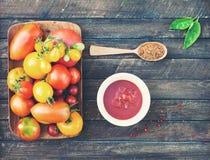 Красочные органические томаты в деревянной плите с кетчуп spices Стоковая Фотография