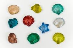 Красочные орнаменты seashell сделанные из изолированного стекла на задней части белизны Стоковое Фото