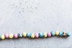 Красочные пасхальные яйца лежа на серой конкретной предпосылке Плоское положение Взгляд сверху Принципиальная схема праздника уст стоковое фото