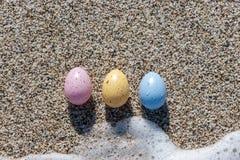 Красочные пасхальные яйца на взморье в солнечном дне Стоковые Фото