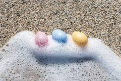 Красочные пасхальные яйца на взморье в солнечном дне Стоковые Фотографии RF