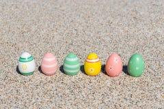 Красочные пасхальные яйца на пляже в солнечном дне Стоковые Изображения RF