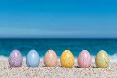 Красочные пасхальные яйца на пляже в солнечном дне Стоковое Фото