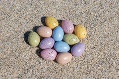 Красочные пасхальные яйца на пляже в солнечном дне Стоковая Фотография