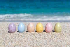 Красочные пасхальные яйца на пляже в солнечном дне Стоковое фото RF