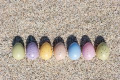 Красочные пасхальные яйца на пляже в солнечном дне Стоковые Фотографии RF