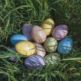 Красочные пасхальные яйца на траве в солнечном дне Стоковая Фотография