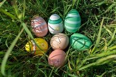 Красочные пасхальные яйца на траве в солнечном дне Стоковые Изображения RF