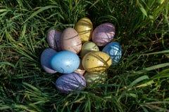 Красочные пасхальные яйца на траве в солнечном дне Стоковые Фотографии RF