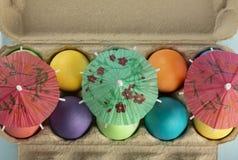 Красочные пасхальные яйца под парасолем в коробке стоковое изображение