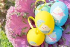 Красочные пасхальные яйца стоя на фиолетовой капусте, подготавливают для охотника яичка традиционного Стоковое Фото