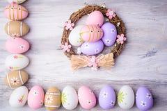 Красочные пасхальные яйца в гнезде на старой треснутой деревянной предпосылке Стоковая Фотография RF