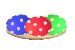Красочные пасхальные яйца в деревянной плите изолированной на белизне стоковая фотография