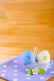 Красочные пасхальные яйца в корзине с цветком на ткани на деревянном b Стоковая Фотография