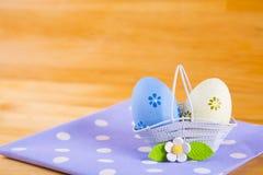 Красочные пасхальные яйца в корзине с цветком на ткани на деревянном b Стоковые Изображения