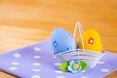 Красочные пасхальные яйца в корзине с цветком на ткани на деревянном b Стоковые Фотографии RF