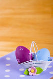 Красочные пасхальные яйца в корзине с цветком на ткани на деревянном b Стоковое Изображение