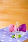 Красочные пасхальные яйца в корзине с цветком на ткани на деревянном b Стоковое фото RF