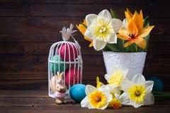 Красочные пасхальные яйца в клетке птицы, декоративном кролике и цветке Стоковая Фотография RF