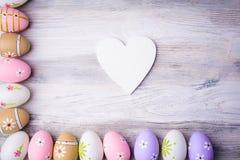 Красочные пасхальные яйца и белое сердце с космосом экземпляра Стоковое Фото