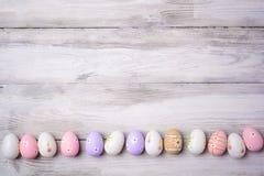 Красочные пасхальные яйца на старой треснутой деревянной предпосылке Стоковая Фотография