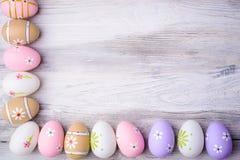 Красочные пасхальные яйца на старой треснутой деревянной предпосылке Стоковое Изображение