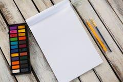 Красочные палитра, paintbrush, карандаш и книга на деревянной поверхности Стоковые Изображения RF