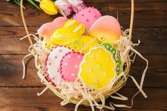 Красочные печенья зайчика и яичка пасхи в корзине на деревянном ба Стоковое Изображение RF