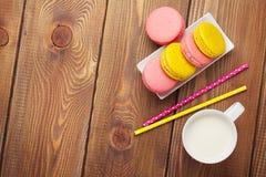 Красочные печенья macaron и чашка молока Стоковая Фотография
