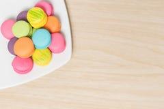 Красочные печенья macaroons в блюде на древесине с космосом экземпляра Стоковое Изображение