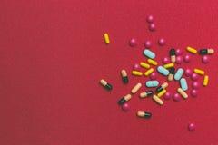 Красочные пилюльки, таблетки и капсулы на красной предпосылке с космосом стетоскоп дег микстуры лож принципиальной схемы установл Стоковые Фотографии RF