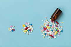 Красочные пилюльки лекарства на голубой предпосылке, увеличивая пользе и злоупотреблении лекарства в мировоззренческой доктрине Стоковые Фотографии RF
