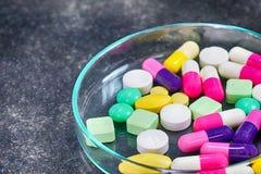 Красочные пилюльки медицины в чашка Петри на таблице Стоковое Фото