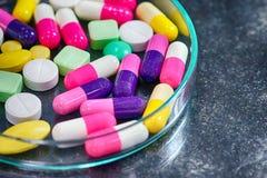 Красочные пилюльки медицины в чашка Петри на таблице Стоковое Изображение RF