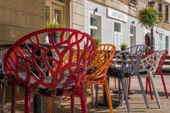 Красочные пластиковые стулья на солнечной террасе кафа стоковое фото rf