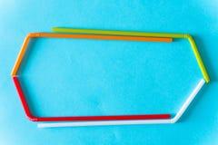 Красочные пластиковые трубки коктейля над голубой предпосылкой Линии конспекта красочные раскосные стоковая фотография