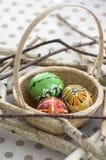 Красочные покрашенные пасхальные яйца в коричневой плетеной корзине на ветвях, традиционном натюрморте пасхи, деревянные птицы гн Стоковое Фото