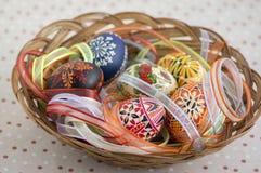 Красочные покрашенные пасхальные яйца в коричневой плетеной корзине покрытой с красочными лентами, традиционном натюрморте пасхи стоковая фотография rf