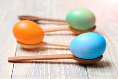 Красочные покрашенные яичка, деревянные ложки, варя и печь, еда пасхи Стоковые Фото