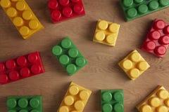 Красочные пластичные блоки конструкции на деревянной предпосылке Плоское положение Взгляд сверху Стоковое фото RF